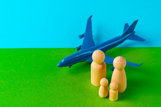 Conceito de viagens e férias em família. figuras de madeira da família e avião de brinquedo