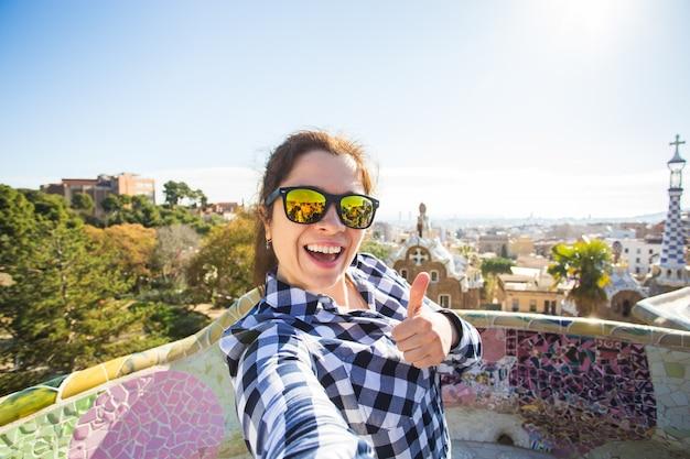 Conceito de viagens e férias - jovem mulher feliz fazendo selfie retrato com smartphone no parque guell