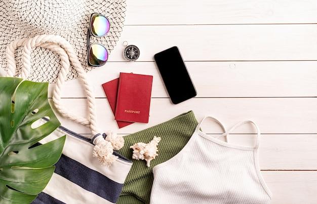 Conceito de viagens e férias. objetos de viagem planos leigos com maiô, smartphone, passaportes, óculos de sol e bússola em fundo branco de madeira