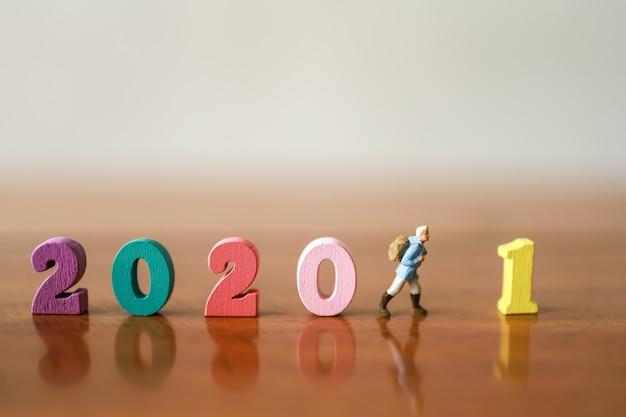Conceito de viagens e viagens de ano novo 2021. pessoas de figura em miniatura de viajante com mochila andando com número de madeira colorido na mesa de madeira.