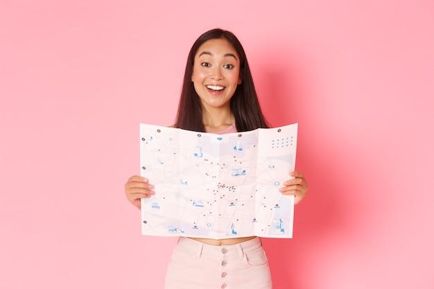 Conceito de viagens, estilo de vida e turismo. turista alegre e atraente garota asiática explorar a nova cidade, visitando museus, mostrando o mapa da cidade com pontos turísticos e sorrindo otimista, fundo rosa.