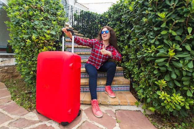 Conceito de viagens, férias e feriados - mulher viajante feliz sentada na escada com óculos de sol