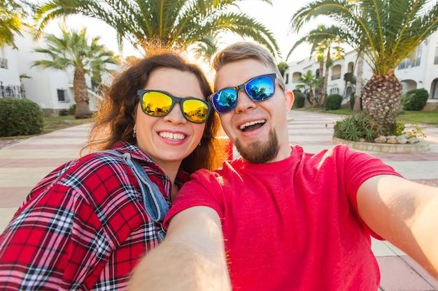 Conceito de viagens, férias e férias - casal engraçado em óculos de sol, se divertindo e tomando selfie.