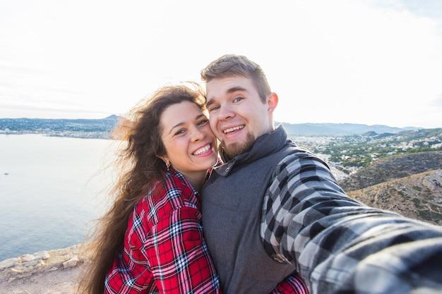 Conceito de viagens, férias e férias - casal feliz tomando selfie sobre a bela paisagem.