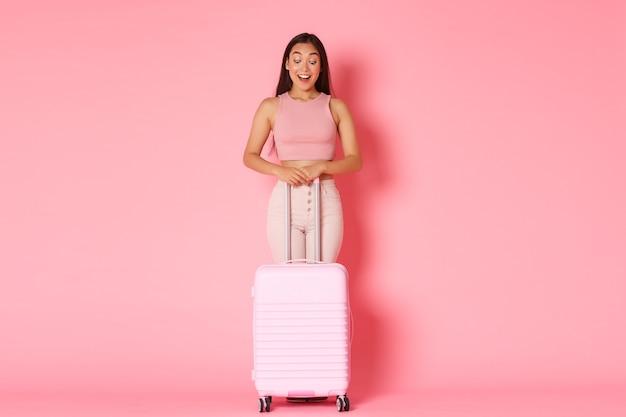 Conceito de viagens, férias e férias. comprimento total de uma garota asiática atraente animada e impressionada