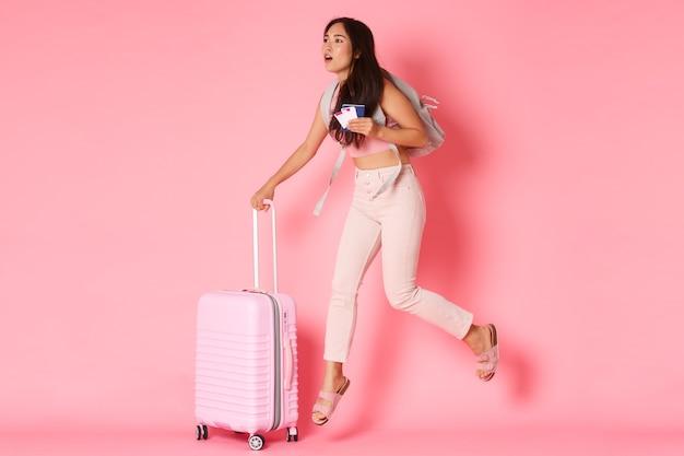 Conceito de viagens, férias e férias. comprimento total de uma garota asiática preocupada se atrasando para o voo, correndo pelo aeroporto com mala, passaporte e passagens de avião, parede rosa