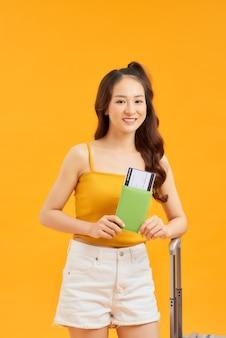 Conceito de viagens. menina mulher feliz com mala e passaporte em fundo laranja