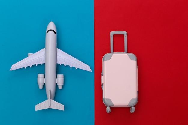 Conceito de viagens. mini mala de viagem de plástico, avião de ar sobre fundo azul vermelho. estilo mínimo. vista do topo. postura plana