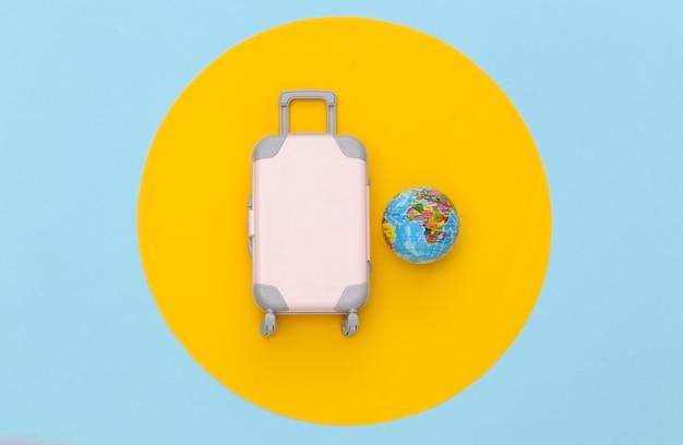 Conceito de viagens. mini mala de viagem de plástico e globo em fundo azul pastel com círculo amarelo. estilo mínimo. vista superior, configuração plana