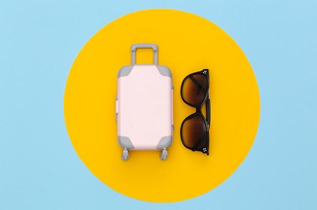 Conceito de viagens. mini mala de viagem de plástico e óculos de sol sobre fundo azul pastel com círculo amarelo. estilo mínimo. vista superior, configuração plana