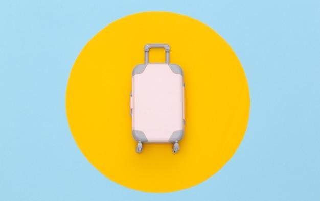 Conceito de viagens. mini mala de viagem de plástico em fundo azul pastel com círculo amarelo. estilo mínimo. vista superior, configuração plana