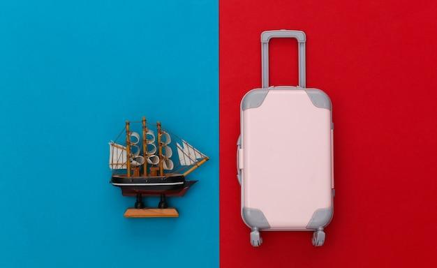 Conceito de viagens. mini mala de viagem de plástico, enviar sobre fundo azul vermelho. estilo mínimo. vista do topo. postura plana