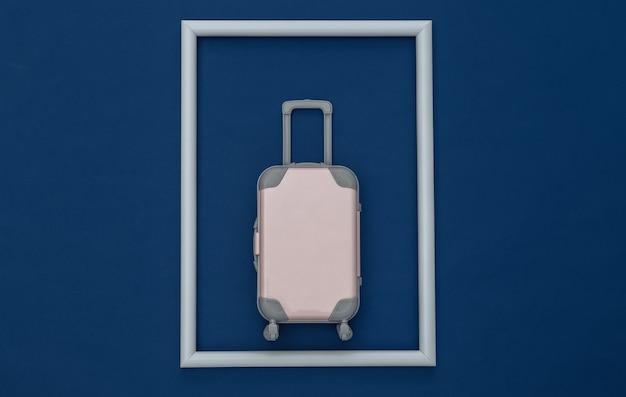 Conceito de viagens. mini mala de viagem de plástico no fundo azul clássico com moldura branca. estilo mínimo. vista superior, configuração plana