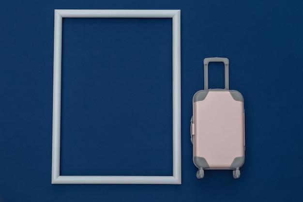 Conceito de viagens. mini mala de viagem de plástico no fundo azul clássico com moldura branca para o seu texto. estilo mínimo. copie o espaço. vista superior, configuração plana