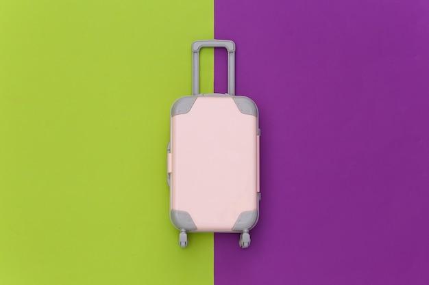 Conceito de viagens. mini mala de viagem de plástico sobre fundo roxo verde. estilo mínimo. vista superior, configuração plana