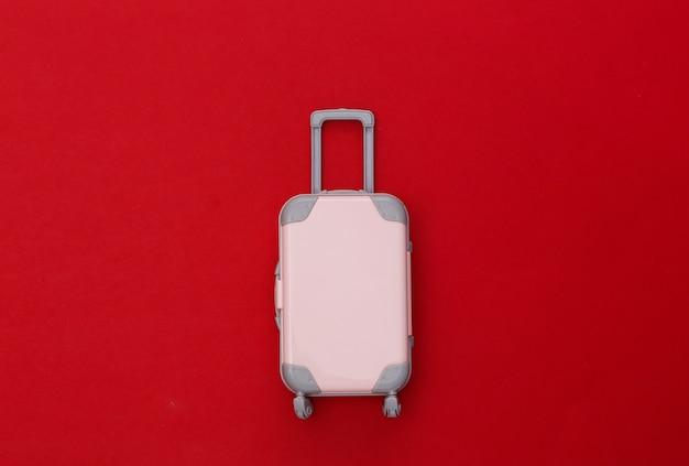 Conceito de viagens. mini mala de viagem de plástico sobre fundo vermelho. estilo mínimo. vista superior, configuração plana