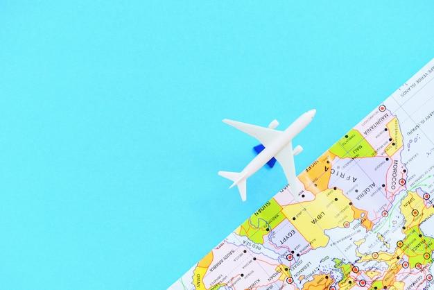 Conceito de viagens - mosca do viajante de avião com turismo de avião e mapa em azul