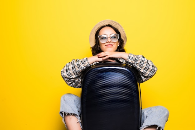 Conceito de viagens. mulher feliz turista com óculos escuros e chapéu vestindo roupas jeans prontas para viajar abraço mala isolada.
