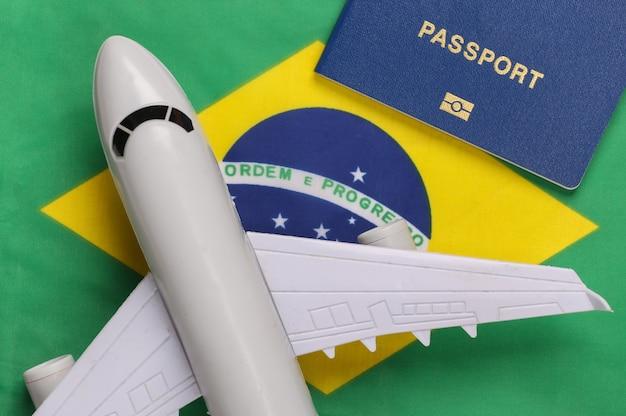 Conceito de viagens. passaporte e avião no contexto da bandeira do brasil