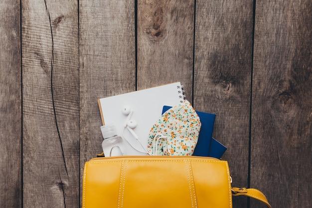 Conceito de viagens plana leiga com passaportes na bolsa de mão, máscara protetora e desinfetante, bloco de notas e fones de ouvido com fundo de madeira.