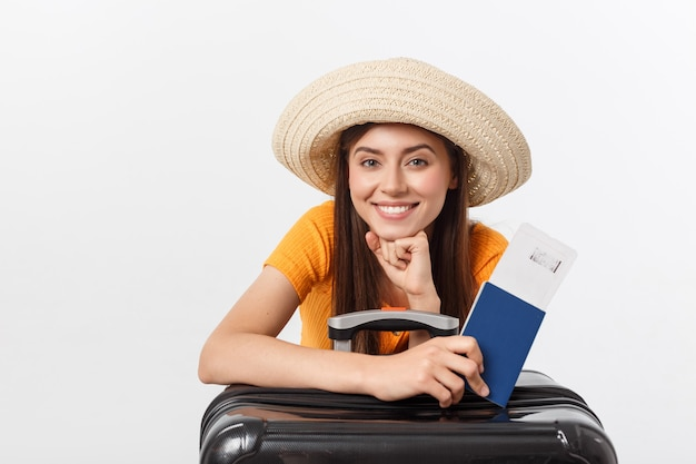 Conceito de viagens. retrato de estúdio da bela jovem segurando o passaporte e bagagem. isolado no branco