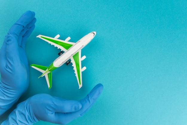 Conceito de viagens seguras. avião nas mãos em luvas médicas. voo seguro e viagens durante a quarentena e o bloqueio.