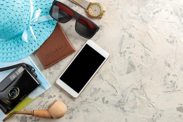 Conceito de viagens smartphone, passaporte, mapa, câmara fotográfica e óculos de sol. vista do topo