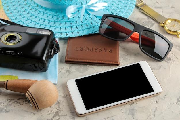 Conceito de viagens smartphone, passaporte, mapa, câmara fotográfica e óculos de sol.