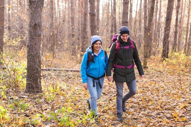 Conceito de viagens, turismo, caminhada e pessoas - casal com mochilas caminhando na floresta de outono.