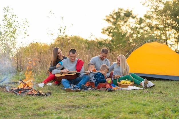 Conceito de viagens, turismo, caminhada, piquenique e pessoas - grupo de amigos felizes com barraca e bebidas tocando violão no camping