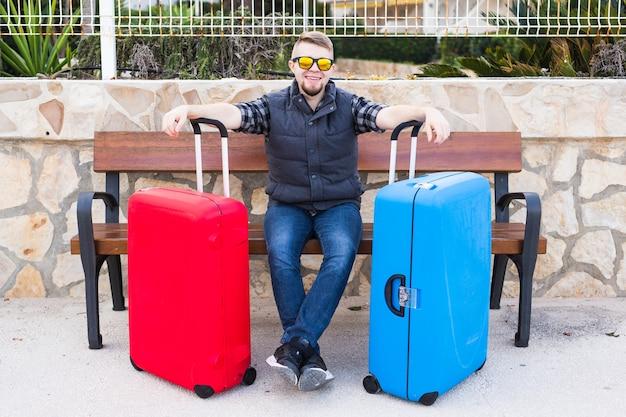 Conceito de viagens, turismo e pessoas - homem feliz sentado em um banco com duas malas, ele está pronto para viajar.