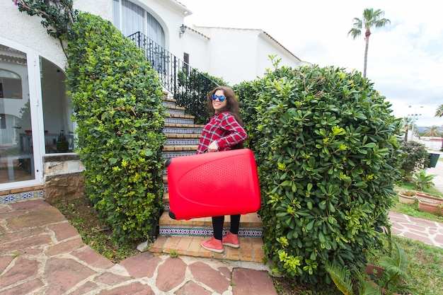 Conceito de viagens, turismo e viagem. jovem feliz subindo as escadas com mala vermelha e sorrindo.
