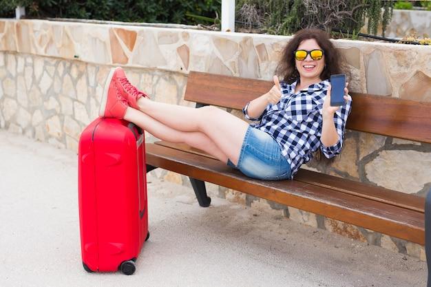 Conceito de viagens, turismo, tecnologia e pessoas. jovem feliz sentar no banco e colocar os pés na mala e mostrando o telefone.