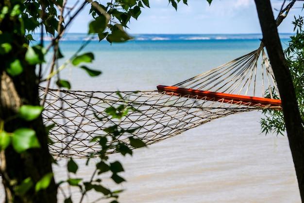 Conceito de viagens. uma rede vazia à sombra das árvores em uma praia tropical com água turquesa ao fundo. lugar aconchegante romântico à sombra das árvores à beira-mar