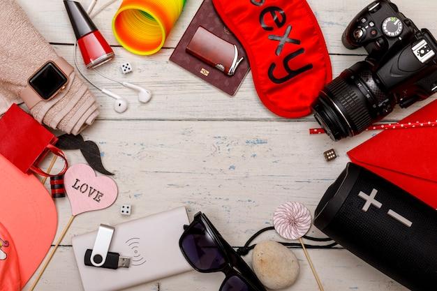 Conceito de viajante. passaporte, carteira, óculos, câmera, alto-falante bluetooth, powerbank, dispositivos de fone de ouvido, sobre um piso de madeira branco. copie o espaço