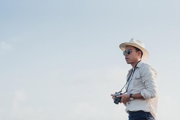 Conceito de viajante: um homem asiático segurando uma câmera em seu telefone ansioso para tirar uma foto contra um fundo branco do céu.