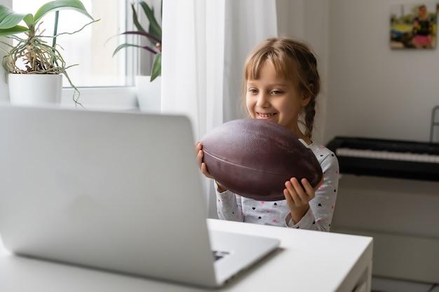 Conceito de vício em internet e computadores com criança e laptop, menina com bola de rugby