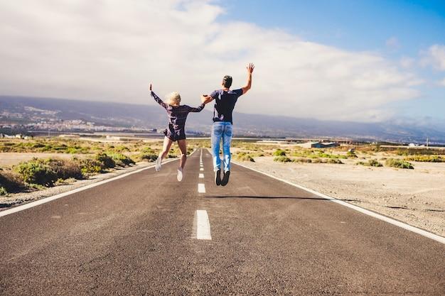 Conceito de vida juntos com dois jovens vistos de costas pulando felizes juntos em uma estrada longa e reta, de mãos dadas e curtindo - céu azul e montanhas ao fundo