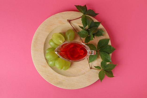 Conceito de vinagre de uva em fundo rosa