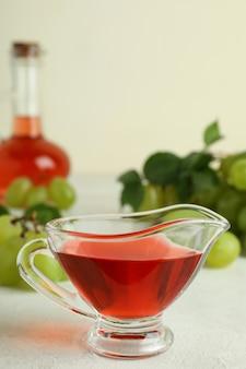Conceito de vinagre de uva em mesa texturizada branca