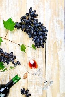 Conceito de vinho tinto com garrafa, copo e uvas