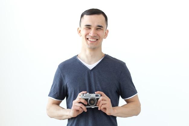 Conceito de vintage, fotógrafo e pessoas - homem bonito com câmera retro, sobre uma superfície branca com espaço de cópia.