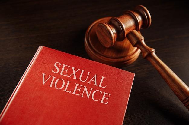 Conceito de violência sexual. martelo de madeira no grande livro vermelho.