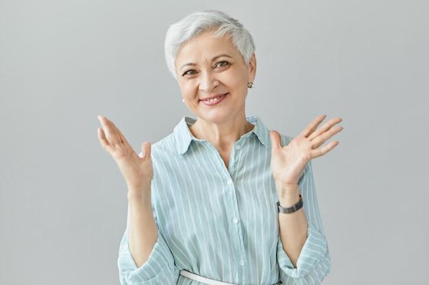 Conceito de vitória, sucesso e realização. mulher aposentada madura eufórica e feliz comemorando a compra bem-sucedida, uma grande notícia positiva, fazendo gestos com as mãos e sorrindo amplamente