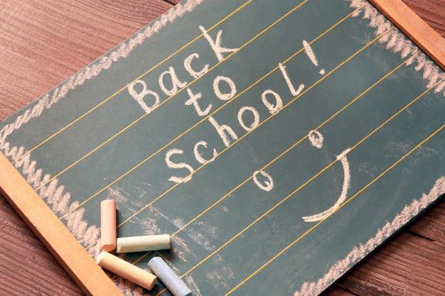 Conceito de volta à escola. quadro-negro com texto volta para a escola, escrita com giz