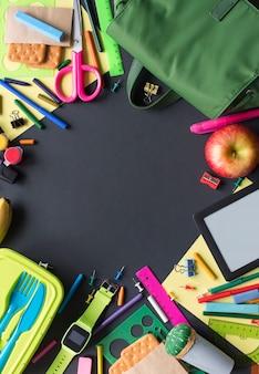 Conceito de volta aos artigos de papelaria da trouxa da maçã da escola no fundo preto.