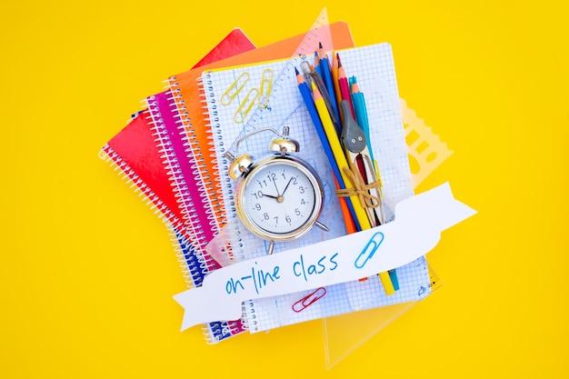 Conceito de volta às aulas - despertador na pilha de cadernos, copie o espaço no fundo amarelo com saudação de volta às aulas