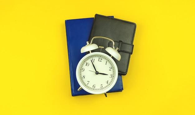 Conceito de volta às aulas, fundo de tempo de educação de alunos com despertador e cadernos diários na mesa amarela, foto de vista superior