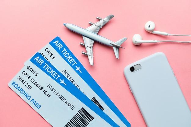 Conceito de voo internacional com bilhetes, avião e smartphone em um fundo rosa