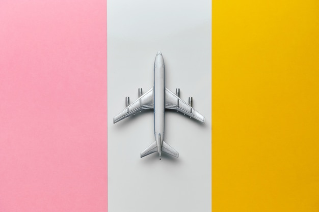 Conceito de vôos internacionais com brinquedo avião sobre um fundo colorido.